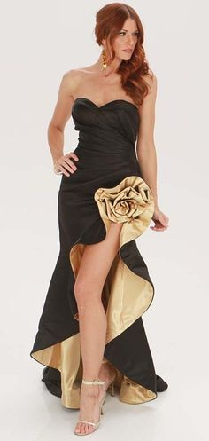 Take peoples breathe away as you enter in this Terani gold and black dress. This sexy piece features a sweetheart neckline, pleats in the mid bodice, and a fantastic gold flower detail on the left side that shows just the right amount of skin and giving this piece a dramatic look.     Color: Black & Gold  Fabric: 100% polyester   $60.00