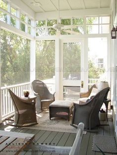Wicker rocking chairs form a seating area on a screened-in porch. - Picmia