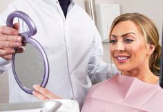A Woman Views Her Smile In A Mirror Dental Insurance Plans