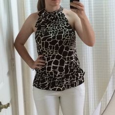 """Giraffe Print Halter Top Super cute halter top with unique print. The cinched in ruffled bottom make this really flattering on many body types and the bow adds a fun touch. Pair with white pants and you have a winner! 24 inches long and at a fitted waist I normally wear a 28"""". The large is due to being purchased in the junior section! Tempted Tops"""