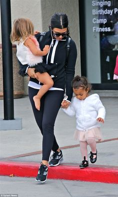 Prima ballerina: The only child of Kanye Westcovered up her dance attire with a fluffy white hoodie jacket and rounded out her cute costume with strappy black tap shoes