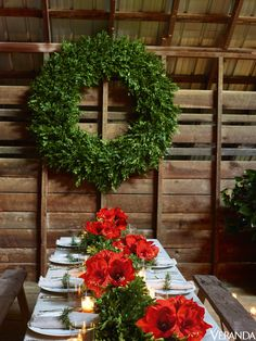 A table is decorated in classic green garlands and red flowers and a boxwood wreath is left unadorned to showcase its large scale at this romantic Christmas dinner party in a rustic Georgia barn.