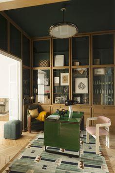 Au centre du cabinet de travail,architecturé par des vitrines, une table modulable dessinée par les décorateurs fait office de bureau et de table de salle à manger. Sur la table une lampeSnoopyde Flos. La chaisePamplonad'Augusto Savini vient de la Galerie Italienne. Le pouf, tout comme le tapis ont été trouvés à la Galerie Triff. Au plafond un lustre Bauhaus (Zeitlos-Berlin).
