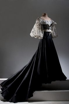 Patis Tesoro. A meld of traditional Filipino styles and modern cuts. Pineapple fiber top with embroidery and sheer black long skirt.