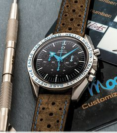 """OMEGA SPEEDMASTER """"HELLO"""" CUSTOMIZED BY MOONTIME ST 145.0222 Made in a limited edition of 10 pieces in 2015. Accompanied by a plastic custom suitcase with Moontime warranty card, spare Omega stainless steel bracelet and strap changing tool. Dial, case and movement signed."""