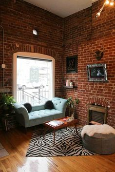 Warm industrial design. Love the exposed brick which is complemented by eclectic vintage pieces including the aqua lounge, zebra print rug, leather pouf, wool throw & antlers.