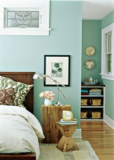 Beautiful guest room with wood floor, mint wall, and bright, calm colors
