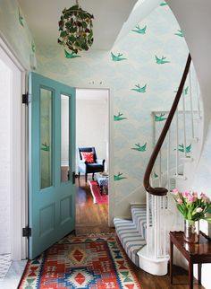 A burst of color in this entryway with a bright blue door, fun rugs and wallpaper!