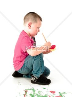 small kid concentrating - Small kid focusing on brushing foam with paint.