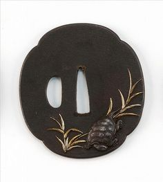"""INLAID IRON MOKKO-FORM TSUBA 18th/19th Century With high-relief depiction of a tortoise and marsh grasses. Length 3"""" (7.7 cm)."""