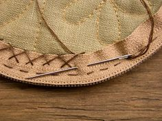 Hand-sewing a zipper into a round bag.