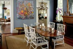 "Dining Room - Charleston Single House Makeover - Southernliving. Rooms in a Single House line up in a row, opening into each other. The Evanses' dining room opens into the living room and kitchen and can be seen from both spaces. ""We color-matched the wall paint to pick up the blues in a swatch of the living room curtain fabric,"" says Angie. The paint color is strong enough to showcase the art and pull together varied furnishings, including Chinese Chippendale rattan and traditional…"