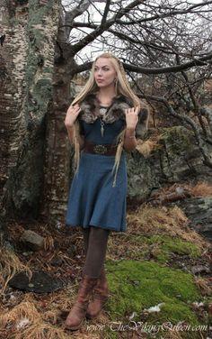 Long blonde hair w/ side braid, faux fur shawl, navy blouse, broad brown belt, aqua midiskirt, brown hose, & kidney brown boots