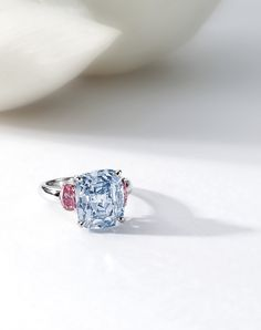 RARE AND IMPORTANT FANCY VIVID BLUE DIAMOND AND PINK DIAMOND RING. Centring on a cushion-shaped fancy vivid blue diamond weighing 6.01 carats, flanked on each side by an oval pink diamond weighing 0.46 and 0.44 carat respectively, mounted in platinum. Estimate 8,993,600 - 10,920,800 USD // LOT SOLD 10,157,629 USD. GIA / 6.01 carats - Fancy Vivid Blue, VVS2 // 0.46 and 0.44 carat - Fancy Vivid Purplish Pink and Fancy Vivid Pink, I1 and VS2 [S. HK - 05 OCT. 2011] #Sotheby's #Vivid #Blue…