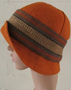 PRE-LOVED VINTAGE Orange hat with brim dating from 1960/70 is made from a firm linen-type fabric with a woven band round the crown. It is in excellent condition and will fit a small to medium sized head.