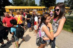 St. John's School student Malena Hernandez, 12,  is hugged by teacher Whitney McKinley outside the Monsignor Gleason building on the last day of school Thursday. Teachers and students will be moving back to an expanded St. John's in September.