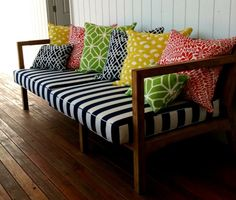 front porch bench inspiration - would be great with actual storage below for coolers and recycling bins.  Love the stripped fabric and graphic pillow combo.