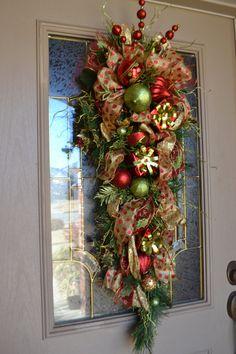 Saludar a tus invitados con este elegante colgante de puerta actual. Está llena de hermosa cinta, ornamentos y presenta en oro y rojo verde. Este colgante medidas 15 x 40.