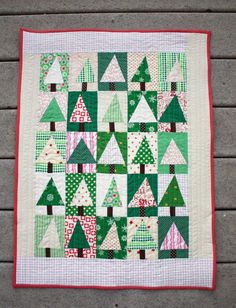 Patchwork Evergreen Quilt - Gather all of your leftover scraps from last years Christmas quilting adventures and prepare to make one of the cutest mini quilt patterns out there. This Patchwork Evergreen Quilt features a hodge podge of adorable little trees in several different colors.