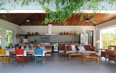 Misture as cores! Na área gourmet deste projeto da arquiteta Eliana Marques Lisboa, a mesa tem cadeiras de tons variados. O sofá ao lado também tem almofadas diferentes entre si. Paisagismo por Alex Hanazak