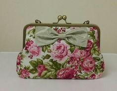 Handmade handbag/clutch bag made from vintage inspired pink rose/green leaves floral quality cotton fabric with a dupion fabric pale green bow on the front.  The lining is a deep raspberry red duch...