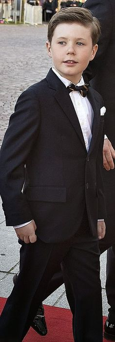 Looking uncannily like a young Frederik, the couple's nine-year-old Prince Christian was also looking very sharp in a midnight blue suit, his hair combed back away from his face just like his father's.