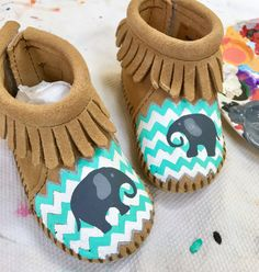 Mint and white custom, handpainted chevron stripes on baby moccasins, size 0-6. I can create any custom color combo depending on the theme of your baby nursery or baby shower. These special keepsake moccasins are meant to be worn, but also as a keepsake in your childs room forever. Available stripes only, or with a design overlay. (Elephants shown.)  Free Range Mama is a free-hand, completely custom, hand-painted collection of keepsake baby booties and moccasins! My personalized shoes make…