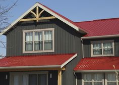 Brown Farmhouse With Red Metal Roof