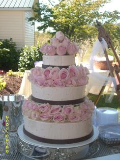 Three tier white buttercream iced wedding cake with brown ribbon and pale pink roses between layers