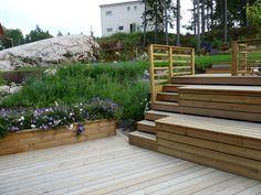 På berghällen bakom huset byggdes en platå upp. En trappa, som planerats för att också kunna användas som sittplats och förvaring, leder upp till platån dit familjen gärna slår sig ner och njuter av det fina kvällsljuset, utsikten över trädgården och omgivningarna.