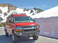 Sportsmobile 4x4 van with Aluminess winch bumper, roof rack, ladder, and other off road accessories.