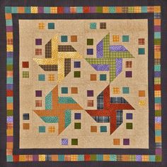 Warm up to a quilt made with cozy flannels and featuring bright pinwheels blowing across the center. The black in the border tones down the bright squares.