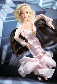 Barbie® salutes the mystique of a classic film with Starring Barbie® doll in King Kong. Inspired by the movie's final, breathtaking moments, she wears a fabulous ensemble reminiscent of the film's original costume. Her gown, of pink charmeuse and chiffon, brings a perfect theatrical flair. Matching pink shoes, a golden faux diamond brooch, and earrings are her glamorous accessories.