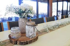 """Save on flowers by simply putting baby's breath or other wintery filler along a table runner and in your silk flower arrangements. Also various sized wooden """"cookies"""" add a natural flair to your centerpieces."""
