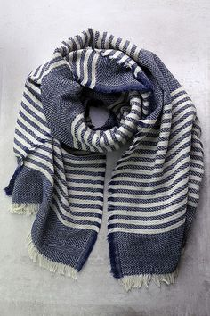 "Mix up equal parts of cuddly and cute and you've got the Cozy Composition Cream and Navy Blue Striped Scarf! Woven knit has a cream and navy blue striped print as it shapes this oversized scarf with fringe ends. Scarf measures 40"" wide, and 80"" long."