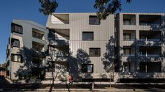 Balconies and windows with projecting black frames punctuate the facades of this apartment complex in Melbourne by Woods Bagot, which is clad in zinc.