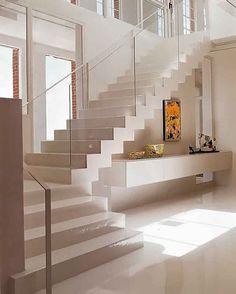 Escada pra se apaixonar. O aparador embaixo da escada e uma forma bastante funcional de aproveitar o espaço.