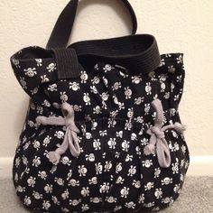 Tillys Skull and cross bones tote Originally purchased from tillys. It didn't have the drawstrings on the front pockets. I added those because the stuff in those pockets kept falling out. Tilly's Bags Totes