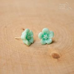 This dainty pair of flower studs are a beautiful shade of teal. They are made with acrylic flowers and hypoallergenic posts. They come with plastic comfort backs.