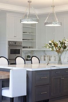 Suzie: Milton Development - Chic two-tone kitchen design with mirrored tiles pendants over ...