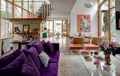 Na sala ampla e clara, o confortável sofá púrpura reina absoluto. Objetos em tons de rosa predominam nos detalhes