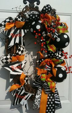 ok, I know this is a Halloween wreath, but picture it with a red, green, and lime green theme, with polkadot ribbons, and matching ornaments w polkadots or swirls...maybe someone would want to make this as their baby gift, and it could go on their front door?!  Maybe there is a way to add some baby items to give it a baby feel?