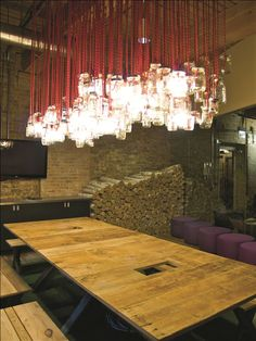 Camp Red Frog's front conference room is lit up by 192 recycled mason jars. The table is custom made out of re-claimed wood from a barn in Kansas.