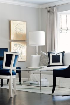Painted ivory dining chairs with contrasting navy velvet balances the sofa and custom toss cushions The gold leaf artwork with acrylic frames are paired with the subtle grey walls  Dining  Living  Transitional by Elizabeth Metcalfe Interiors & Design Inc
