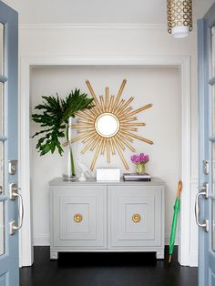 pretty blue door and pops of gold welcome you in this fab foyer!