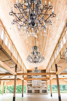 The barn at Homestead Manor is a dramatically designed space perfect for weddings, parties, and a host of other special occasions. Huge crystal chandeliers hang from the tall barn ceilings and a massive local stone fireplace provides an ambience. Interior Design: Kim Leggett, City Farmhouse