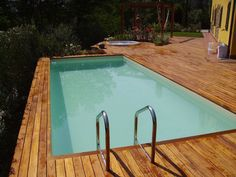 Piscina Dolcevita Gold Interrata con deck in legno che funge anche da bordo vasca. Telo beige e scala inox.