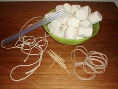 """Small group problem solving: """"You have 2 minutes to devise a method to suspend/hold as many marshmallows above the ground as possible."""" Pts awarded for creativity, building design, and number of marshmallow's successfully suspended. Construction Materials 5' length of string 1 bag of large marshmallows 10 rubber bands 5 straws 10 toothpicks"""