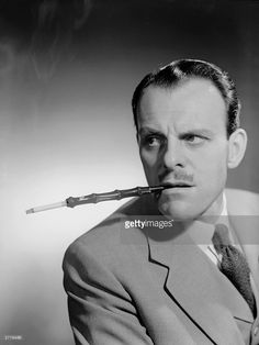 1951: English actor-comedian Terry Thomas (1911 - 1990), real name Thomas Terry Hoar-Stevens, smoking a cigarette in a long holder.