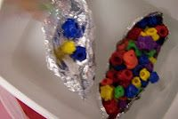 SHIP SHAPE  The students designed a boat using a piece of foil.  Then they tested the buoyancy of their boat by adding frog counters to see how much it will hold before the boat sinks.